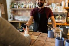 有付款终端和手的人有智能手机的 免版税图库摄影
