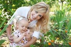 有休息在公园的女儿的愉快的母亲在天 库存图片