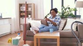 有休息在家庭清洁以后的智能手机的妇女 股票视频