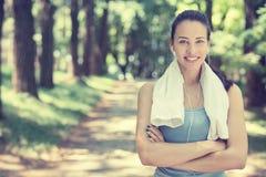 有休息在锻炼以后的白色毛巾的可爱的微笑的适合的妇女 免版税库存照片