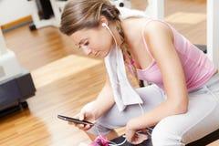 有休息从锻炼的巧妙的电话的微笑的妇女在健身房 库存图片