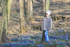 有会开蓝色钟形花的草的女孩 免版税库存照片