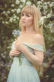 有会开蓝色钟形花的草的妇女 免版税库存照片