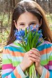 有会开蓝色钟形花的草花束的女孩  图库摄影
