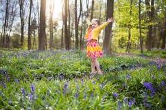有会开蓝色钟形花的草花的孩子在春天森林里 库存图片