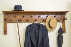 有伞、帽子和外套的老外套机架 免版税库存照片