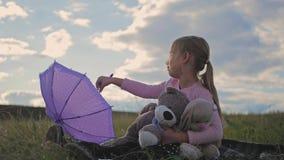 有伞和玩具的愉快的滑稽的小女孩 使用在自然的孩子户外 儿童梦想概念 股票视频