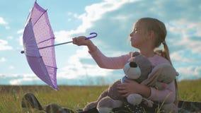 有伞和玩具的愉快的滑稽的小女孩 使用在自然的孩子户外 儿童梦想概念 股票录像