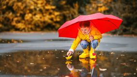 有伞和纸小船的愉快的儿童女孩在a的水坑 免版税库存照片