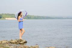 有伞架的孤独的哀伤的女孩在河和调查的银行距离 免版税库存图片