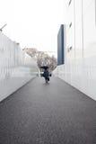 有伞的一名妇女走在狭窄的平直的步行边路的在金属白色墙壁之间 免版税库存图片