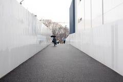 有伞的一名妇女走在狭窄的平直的步行边路的在金属白色墙壁之间 免版税库存照片