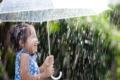 有伞的亚裔小女孩在雨中 图库摄影