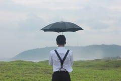 有伞的十几岁的男孩 图库摄影