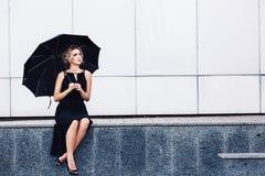 有伞的华美的妇女坐栏杆和等待 库存图片