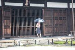 有伞的女孩在日本寺庙 库存图片