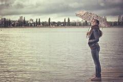 有伞的女孩在水库 库存照片