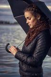 有伞的女孩在水库 免版税库存图片
