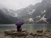 有伞的女孩坐岩石临近湖 库存照片