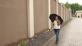 有伞的女孩步行沿着向下街道的 股票录像