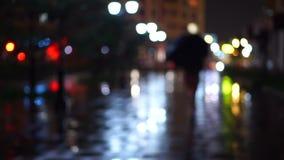 有伞的女孩走在多雨晚上, bokeh录影的 股票录像