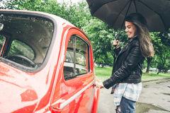 有伞的妇女在红色减速火箭的汽车坐 免版税库存图片