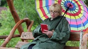 有伞的妇女坐摇摆长凳并且使用智能手机 股票录像