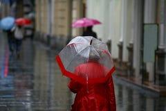 有伞的妇女走在雨中的 免版税库存图片