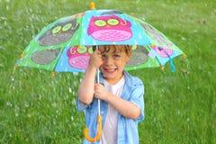 有伞的孩子在雨中 免版税库存图片