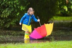 有伞的小女孩在雨中 免版税库存照片