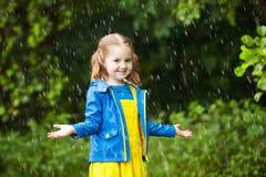 有伞的小女孩在雨中 库存照片