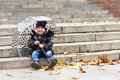 有伞的小微笑的女孩 免版税库存照片
