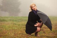 有伞的年轻时尚妇女在室外的雾 免版税库存图片