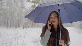 有伞的年轻美丽的妇女谈话在她的在多雪的背景的手机在一个冬天走户外 股票视频