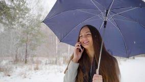 有伞的年轻美丽的妇女谈话在她的在多雪的背景的手机在一个冬天走户外 影视素材