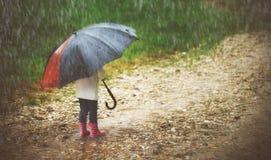 有伞的愉快的女婴在雨中通过跑 免版税库存照片