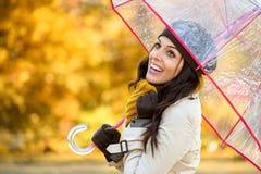 有伞的愉快的妇女在秋天雨下 库存图片