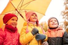 有伞的愉快的孩子在秋天公园 免版税库存照片