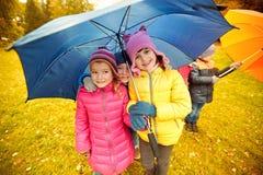 有伞的愉快的孩子在秋天公园 免版税库存图片