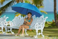 有伞的愉快的小女孩,坐老牌金属长凳 库存图片