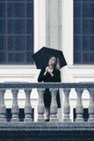 有伞的愉快的年轻时尚妇女走在城市街道的 免版税库存图片