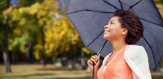 有伞的愉快的非洲妇女在秋天公园 免版税库存图片
