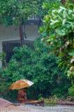有伞的橙色修士在雨中 图库摄影