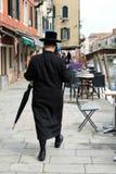 有伞的犹太Hasidic人走在街道的在犹太区 免版税库存图片