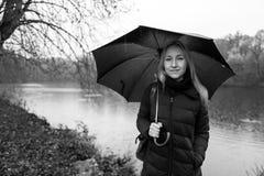 有伞的白肤金发的女孩在Kranichstein,德国 免版税图库摄影