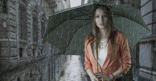 有伞的美丽的妇女在雨之下 库存照片