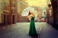 有伞的美丽的少妇在一个老街道镇 库存图片
