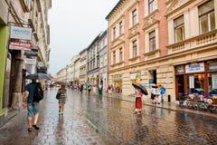有伞的逗人喜爱的妇女走在雨下的在老房子城市 库存图片