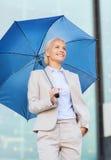 有伞的年轻微笑的女实业家户外 库存照片