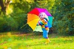 有伞的滑稽的小女孩 免版税库存图片